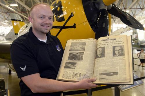 Aaron Clark holding bound newspaper